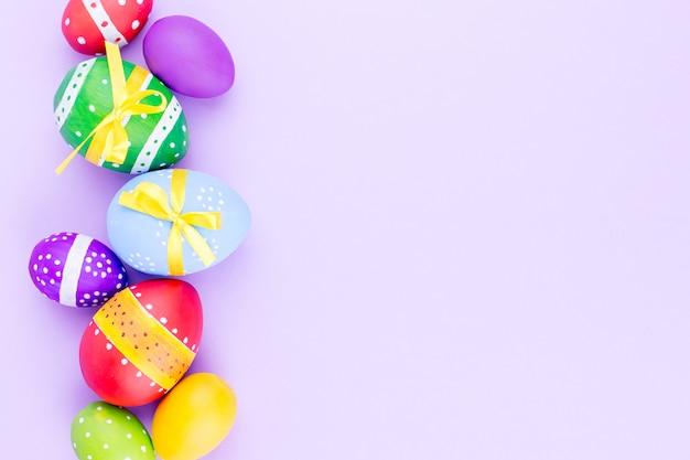 Ovos da páscoa coloridos na configuração pastel do plano do fundo. copie o espaço