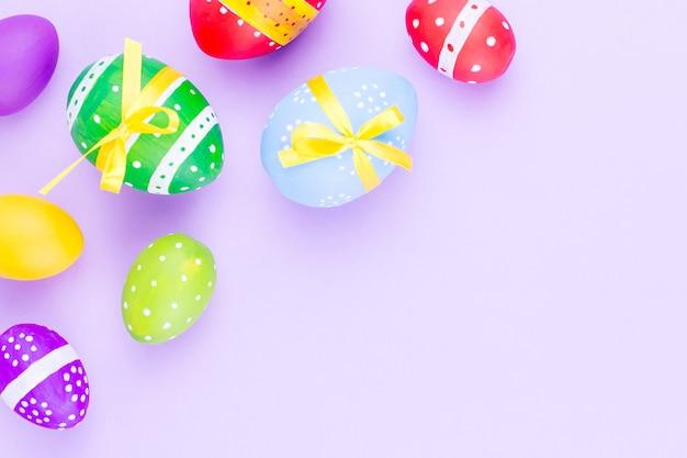 Ovos da páscoa coloridos na configuração roxa pastel do plano do fundo. copie o espaço