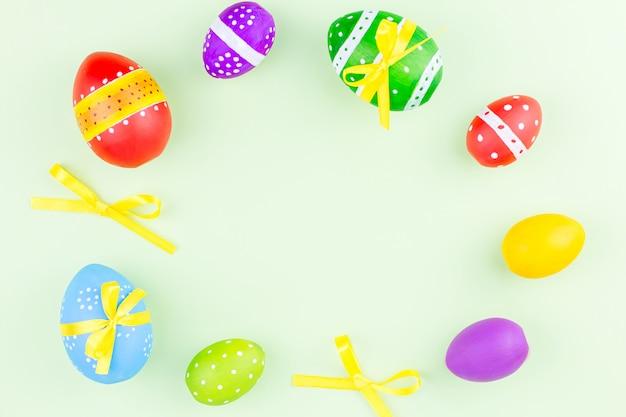 Ovos da páscoa coloridos na configuração verde pastel do plano do fundo. copie o espaço