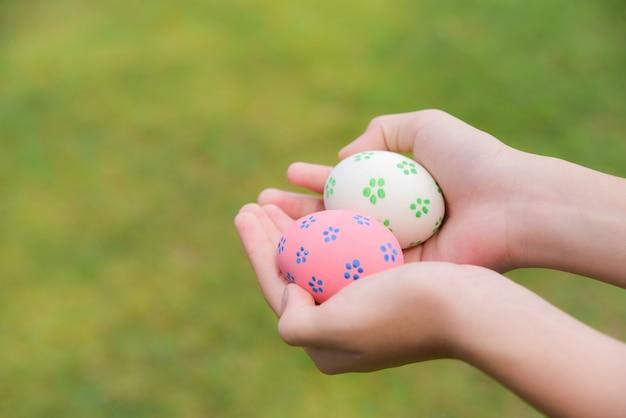 Ovos da páscoa coloridos nas mãos das crianças após a caça do ovo no fundo da grama verde.
