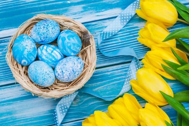 Ovos da páscoa com as tulipas na placa de madeira, conceito do feriado da páscoa. copyspace para texto