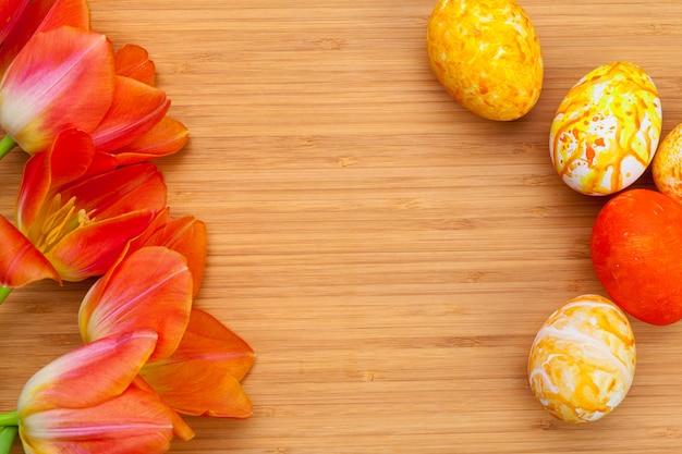 Ovos da páscoa com as tulipas na placa de madeira, conceito do feriado de easter. copyspace