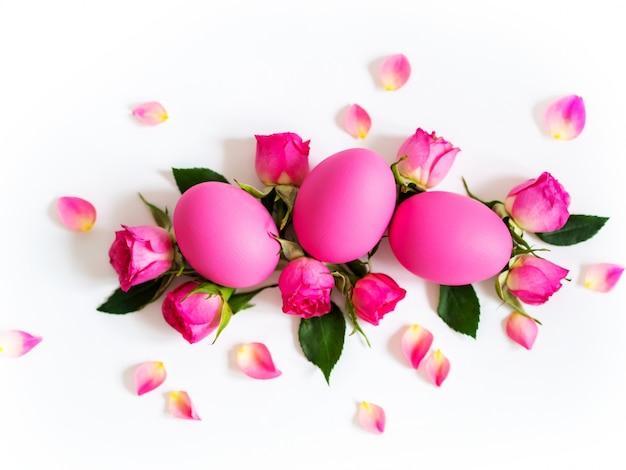 Ovos da páscoa cor-de-rosa no fundo claro com rosas cor-de-rosa. cartão de férias, copie o espaço.