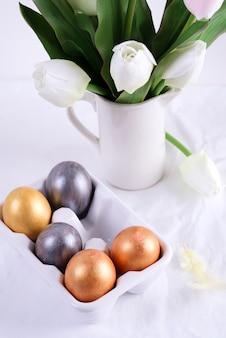Ovos da páscoa dourados na bandeja cerâmica do ovo com a tulipa na tabela branca.
