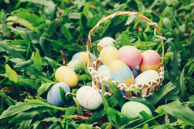 Ovos da páscoa e cesta coloridos na grama verde com luz solar. vintage em tons.