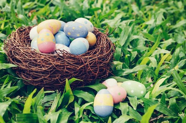 Ovos da páscoa e ninho coloridos na grama verde com luz solar. vintage em tons.