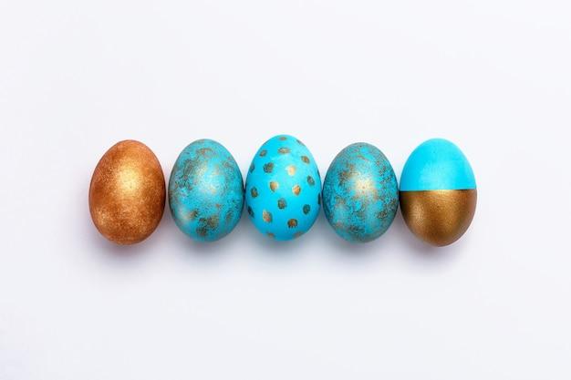 Ovos da páscoa modernos azuis e dourados na linha em um fundo branco. vista do topo. conceito de páscoa isolado.