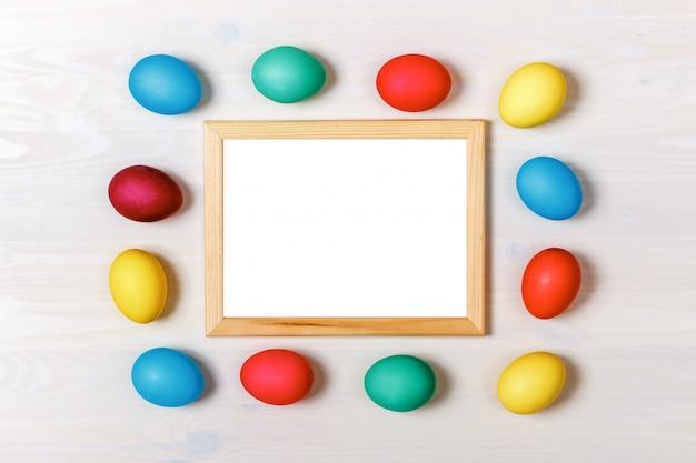 Ovos da páscoa multi-coloridos em torno do quadro em um fundo branco.