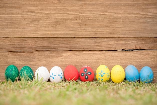 Ovos da páscoa na grama contra de madeira velho borrado.