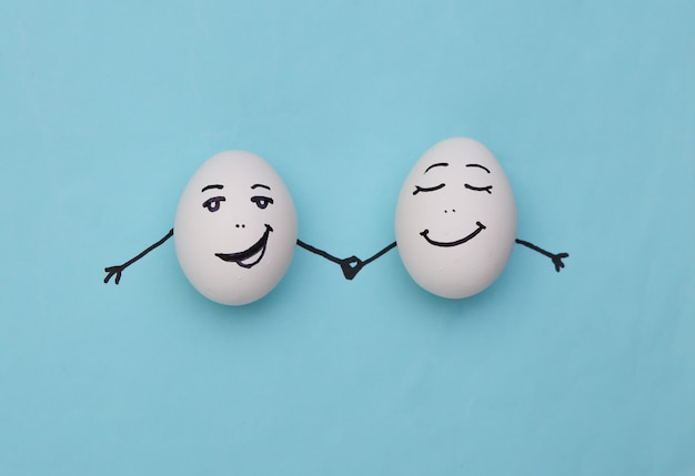 Ovos de casal feliz com rostos desenhados à mão em fundo azul