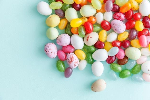 Ovos de chocolate de doces de páscoa e doces de jujubas isolados no azul pastel da moda.