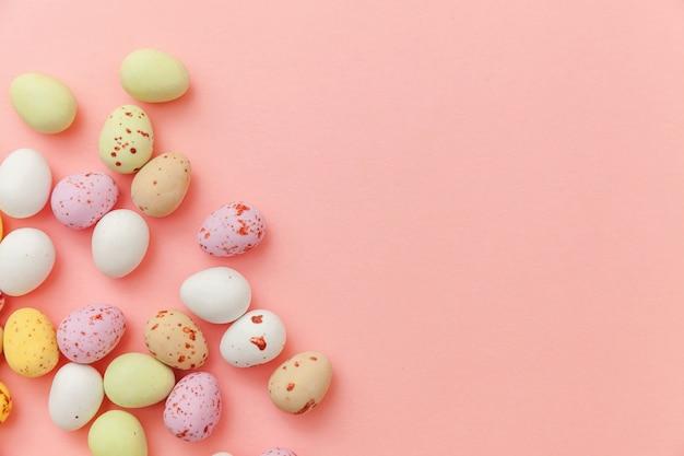 Ovos de chocolate doces de páscoa e balas de balas isoladas em um fundo rosa pastel da moda