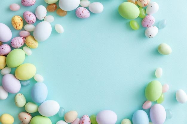 Ovos de chocolate doces de páscoa e balas de geleia isolados na mesa azul