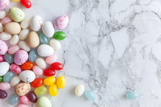 Ovos de chocolate doces de páscoa e balas de geleia no fundo de mármore cinza da moda