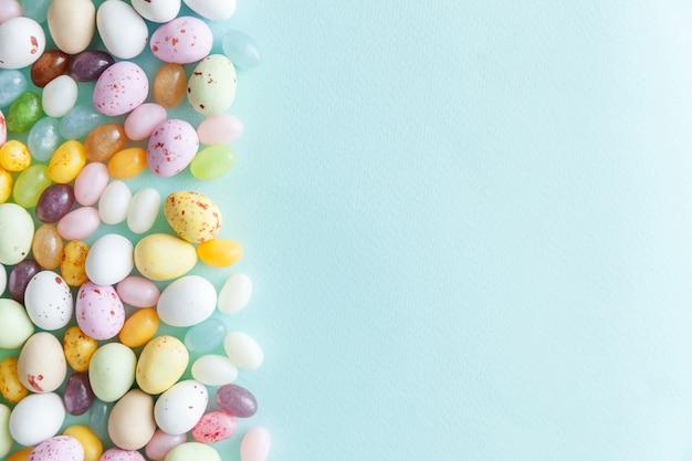 Ovos de chocolate doces de páscoa e balas de goma isoladas sobre fundo azul