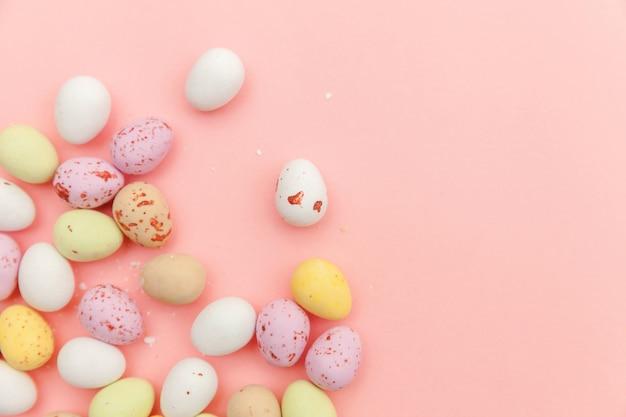 Ovos de chocolate doces de páscoa e doces de balas de geleia isolados na mesa rosa