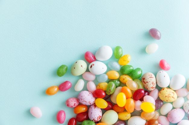 Ovos de chocolate doces de páscoa e doces de jujubas isolados em um fundo azul pastel da moda