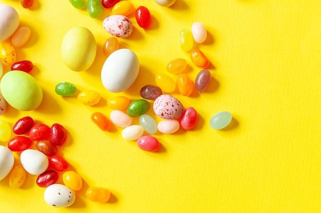Ovos de chocolate doces de páscoa e jujubas isoladas em fundo amarelo