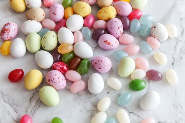Ovos de chocolate e doces de geleia na mesa de mármore cinza da moda