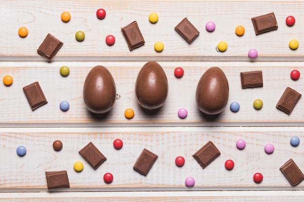Ovos de chocolate inteiros de páscoa; peça e pedras coloridas doces coloridos na mesa de madeira