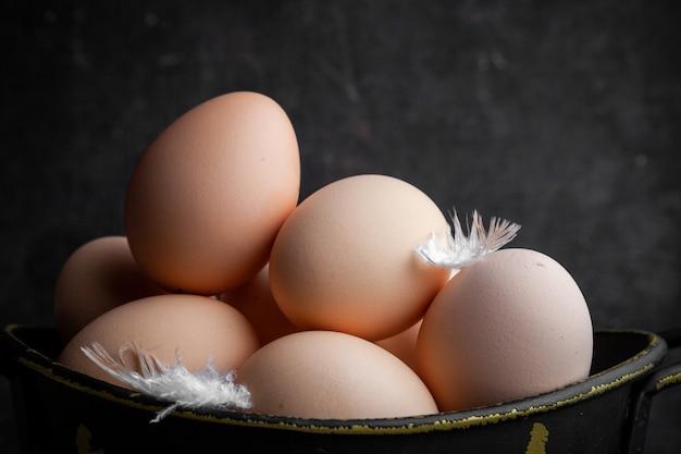Ovos de close-up em panela com penas no fundo escuro de madeira. horizontal