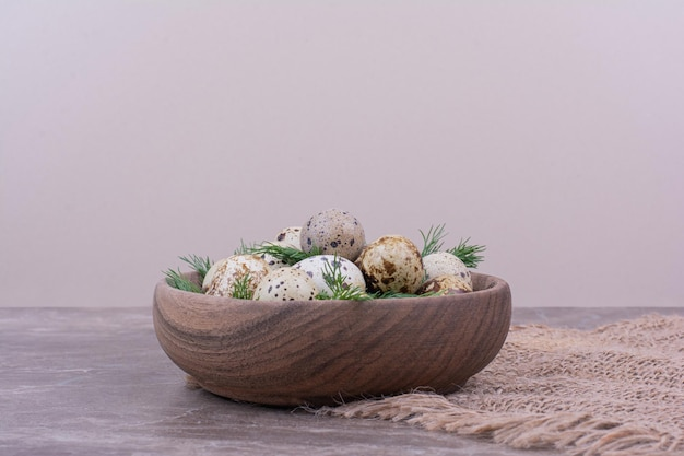 Ovos de codorna com ervas em um copo de madeira.