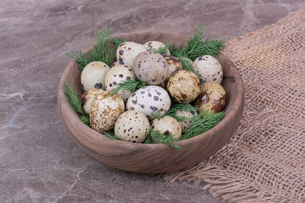 Ovos de codorna com ervas picadas em um copo de madeira