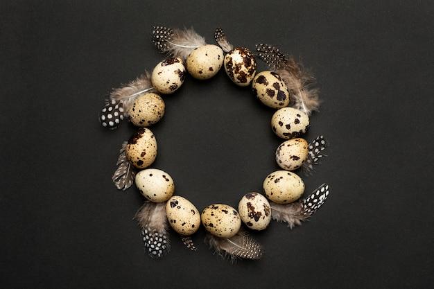 Ovos de codorna com penas em forma de círculo em um fundo preto. férias da páscoa, composição minimalista em preto Foto Premium