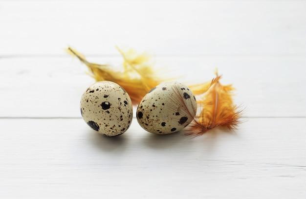Ovos de codorna com penas laranja em fundo de madeira. fundo de feriado de páscoa.