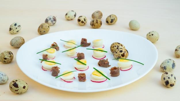 Ovos de codorna cozidos com anchovas e cebolinhas em um prato