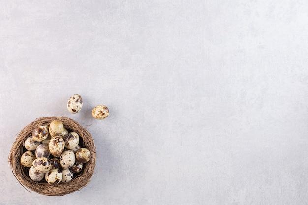 Ovos de codorna crus frescos colocados sobre uma mesa de pedra.