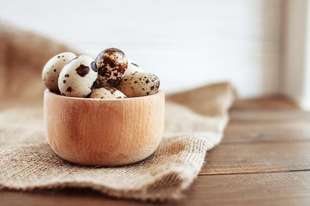 Ovos de codorna de uma tigela de madeira em cima da mesa. de saudável