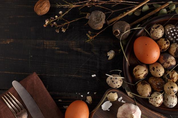 Ovos de codorna e frango em um prato de barro em uma superfície de madeira escura.