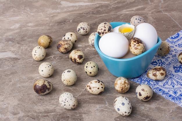 Ovos de codorna e galinha em um copo azul