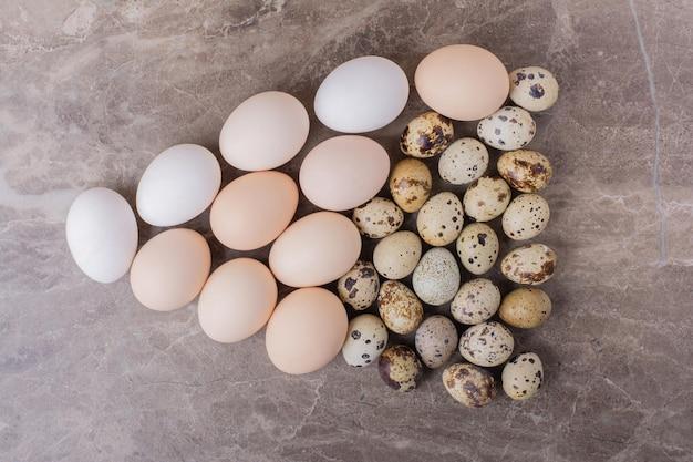 Ovos de codorna e galinha isolados na mesa de mármore.