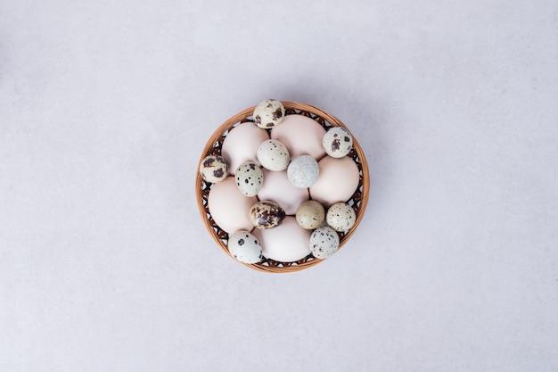 Ovos de codorna e ovos de galinha em uma tigela na superfície branca.