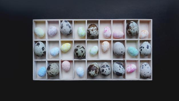Ovos de codorna e ovos de páscoa em recipientes de madeira. vista do topo. fundo preto