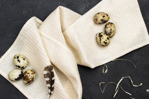 Ovos de codorna e penas em um guardanapo bege. postura plana. copie o espaço