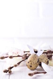Ovos de codorna e selos de ramos em fundo branco de madeira, decorações de páscoa.