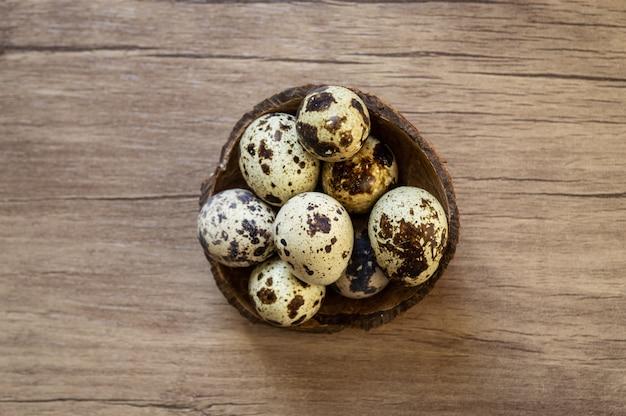 Ovos de codorna em fundo de madeira marrom. flat leigo, vista de cima. conceito de páscoa.