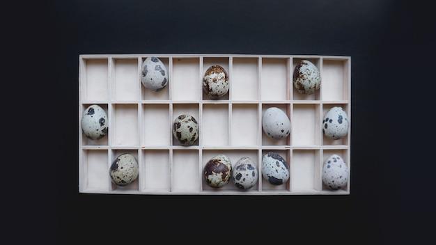 Ovos de codorna em recipientes de madeira. vista do topo. fundo preto