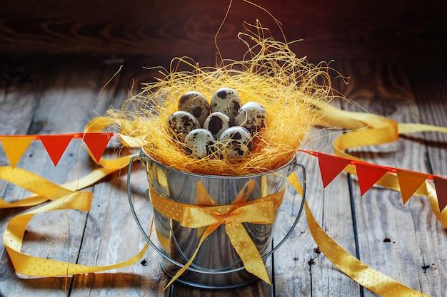 Ovos de codorna em um balde decorado com fitas e etiquetas