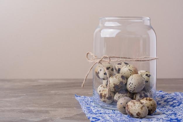 Ovos de codorna em um frasco de vidro na toalha azul