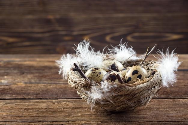 Ovos de codorna em um ninho em uma mesa de madeira.