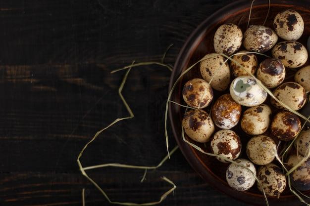 Ovos de codorna em um prato de barro em uma superfície de madeira escura.