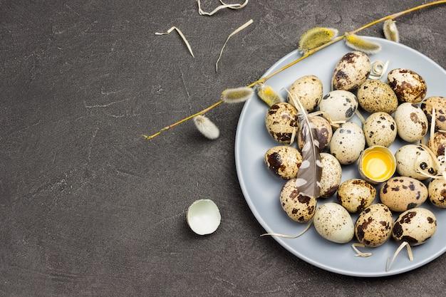 Ovos de codorna em um prato na vista superior de fundo de concreto escuro
