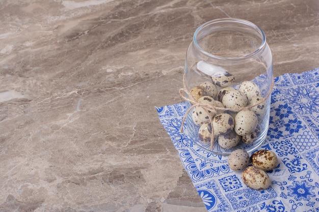Ovos de codorna em um recipiente de vidro no mármore.