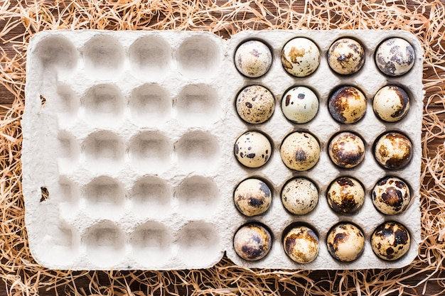 Ovos de codorna em uma caixa e palha em uma vista superior tablein de madeira
