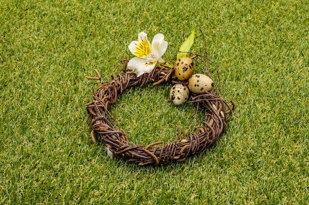 Ovos de codorna em uma coroa de vime na grama verde ensolarada fresca
