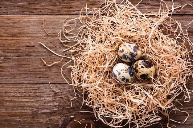 Ovos de codorna em uma pilha de palha em uma vista superior tablein de madeira